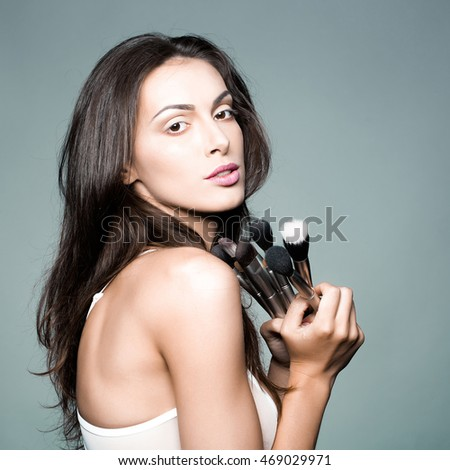 young woman with pretty face and long brunette hair in sexy white bra on body holding fashionable makeup brush set in studio on grey background