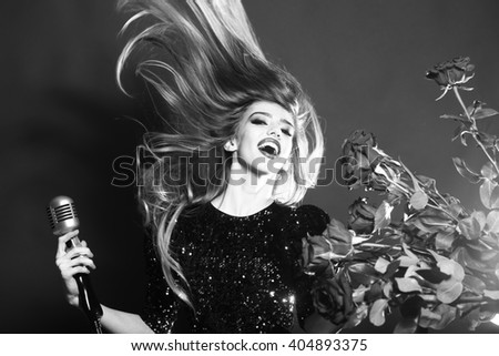 Young woman with pretty happy face holding retro microphone with bouquet of rose flowers, black and white