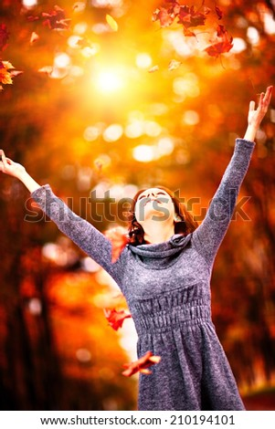Young woman with raised arms throws autumn leaves on sunset - stock photo