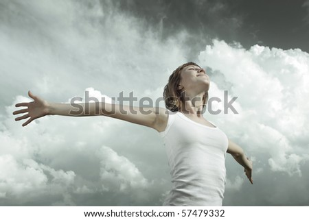 Young woman with raised hands - stock photo