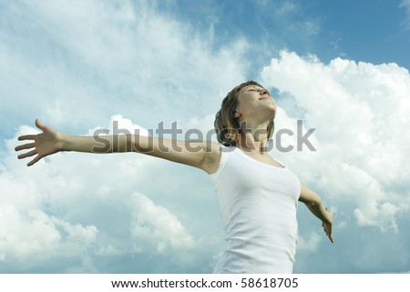 Young woman with raised hands and fluffy sky background - stock photo