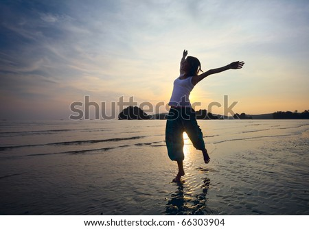 Young woman with raised hands jumping over wet sand - stock photo