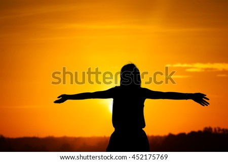 Young woman with raised hands standing on land over sunrise