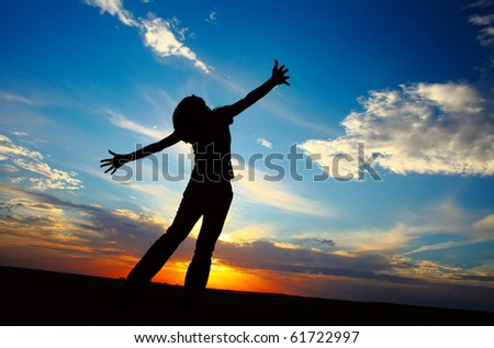 Young woman with raised hands standing on land over sunset light - stock photo