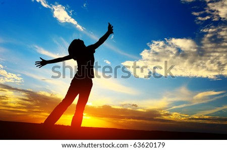 Young woman with raised hands standing on meadow on sunset - stock photo