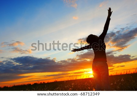 Young woman with raised hands standing on meadow with herbs and looking to a sky - stock photo