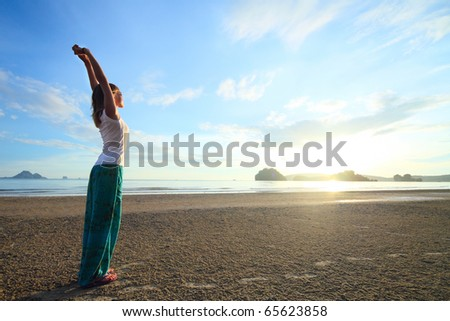 Young woman with raised hands standing on sand and looking to a sky - stock photo