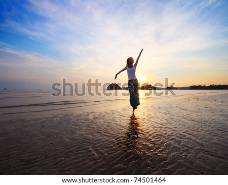 Young woman with raised hands standing on wet sand