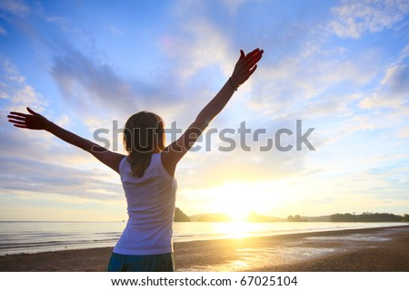 Young woman with raised hands standing on wet sand and looking to a horizon - stock photo