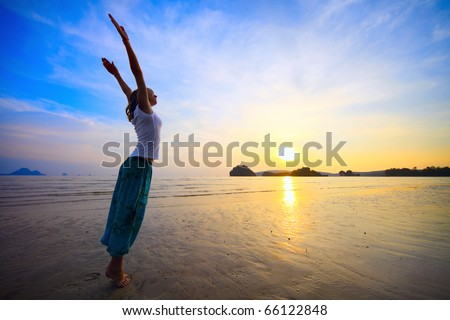 Young woman with raised hands standing on wet sand and looking to a sky - stock photo