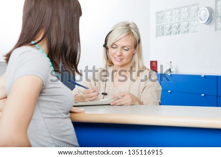 Young woman with receptionist filling form at desk in dentist's office - stock photo