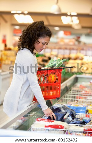 Young woman with red basket buying frozen food in supermarket