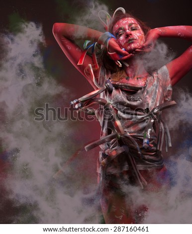 Young woman with red body art wearing a t-shirt with smoke around - stock photo