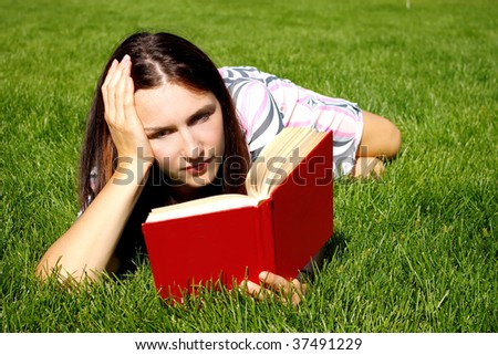Young woman with red book on the green grass