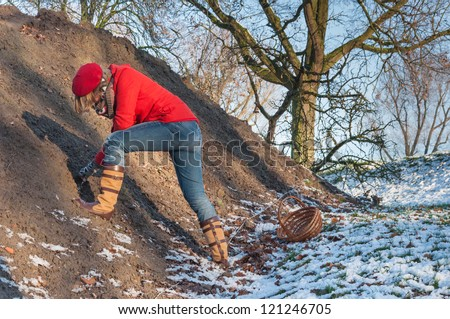 Young woman with red cap and coat searching for ancient shards and the like at a mound of earth on a historical site. - stock photo