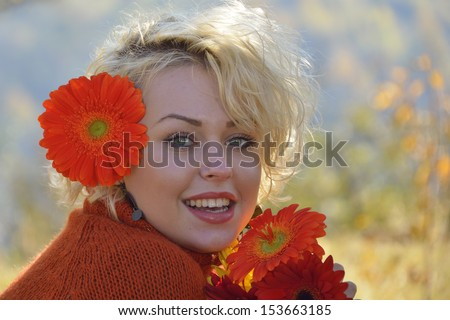 Young woman with red flowers outdoor