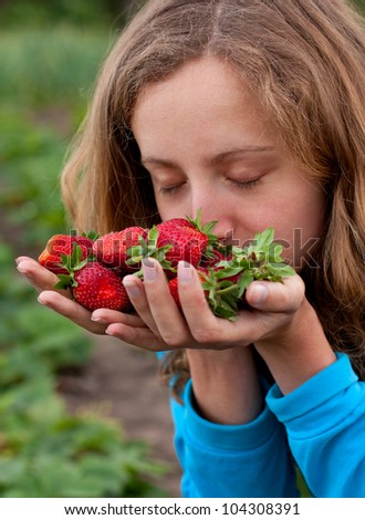 Young woman with red fresh strawberries in hands. Enjoying the aroma of ripe strawberries - stock photo