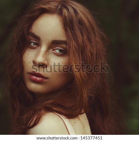 Young woman with red hair outdoors portrait. Soft sunny colors. - stock photo