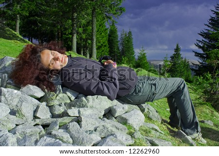 Young woman with red hair relaxing on the mountains