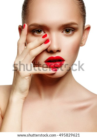 Young woman with red lips and red nails, touching her face isolated on white background