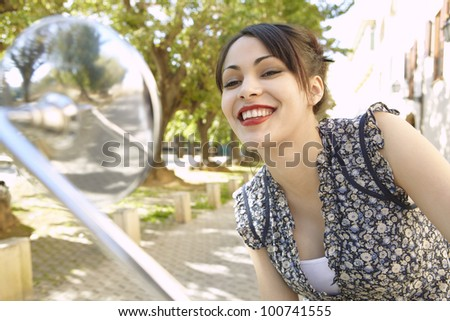 Young woman with red lips looking at herself in a motorbike's mirror in a tree aligned street. - stock photo