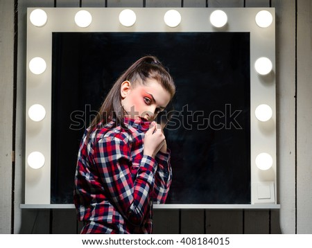 Young woman with red makeup near the mirror. Photo of actress. - stock photo