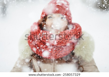 young woman with red scarf playing with snow, selective focus on the snowflakes - stock photo