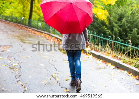 Young woman with red umbrella and yellow leaf in beautiful autumn park