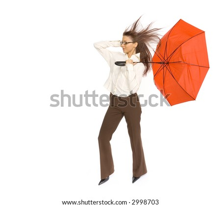 Young woman with red umbrella in hand fighting with strong wind blowing on her. Isolated on white in studio. - stock photo