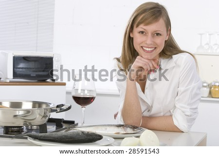 Young woman with red wine at kitchen - stock photo