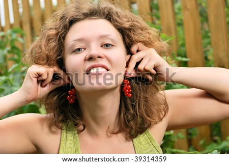 "Young woman with redcurrant berry ""earrings"" - stock photo"