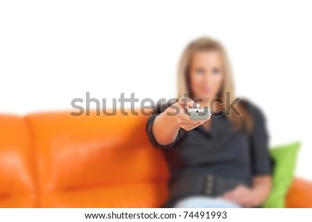 Young woman with remote control on a sofa in her living room. Focused on remote control - stock photo