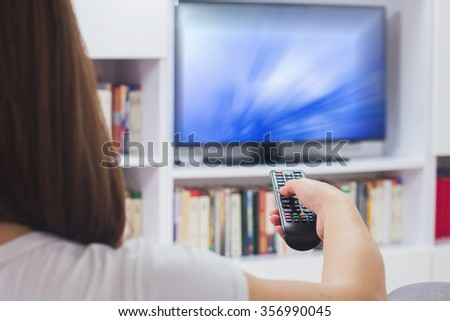 Young woman with remote control, watching TV program at home, - stock photo