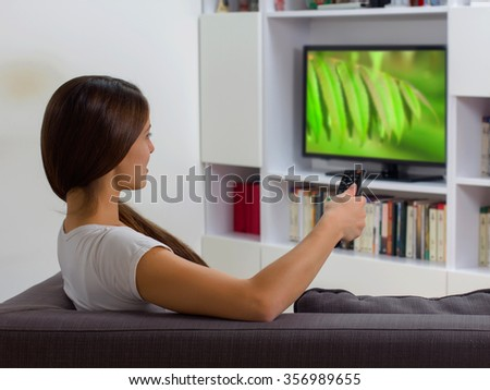 Young woman with remote control, watching TV program at home, Photo on television is from my gallery.
