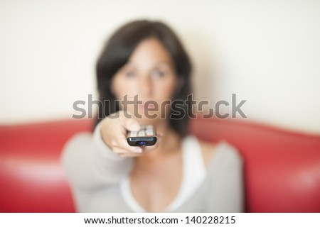 Young woman with remote watching TV. Shallow close-up focused on remote control. - stock photo