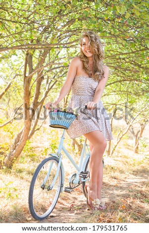 Young woman with retro bicycle in a park - outdoor portrait - stock photo