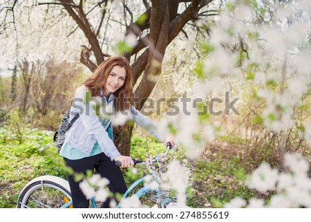 Young woman with retro bicycle in a park - under a blossoming tree - stock photo