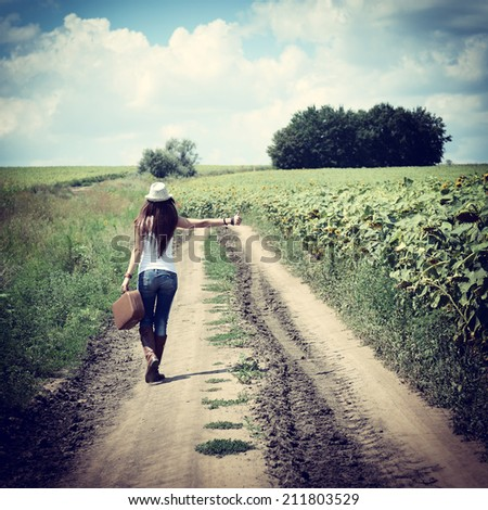 young woman with retro suitcase traveling in countryside, summer nature outdoor, toned - stock photo