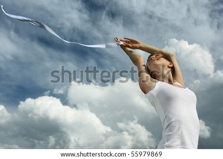 Young woman with ribbon over cloudy background - stock photo