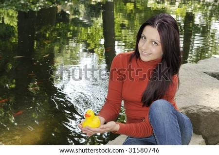 young woman with rubber duck is sitting on a stone - stock photo