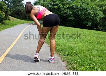 Young woman with running injury on calf - stock photo