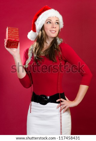 Young Woman with Santa Hat and Gift on red background - stock photo