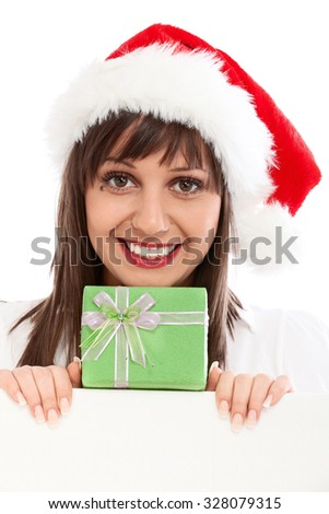Young woman with santa hat and green Christmas gift behind white billboard. Isolated on white background