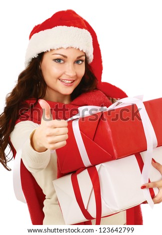 young woman with Santa hat holding  stack of gift and showing ok, isolated on white background