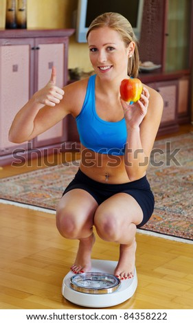 Young woman with scales and apple. Successful Diet - stock photo