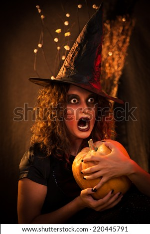 Young woman with scared face dressed like a witch. She wears dark clothing and holding a pumpkin in hands.