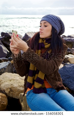 Young woman with scarf and hat taking picture of herself with iphone - stock photo