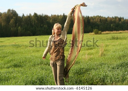 young woman with scarf in a field - stock photo