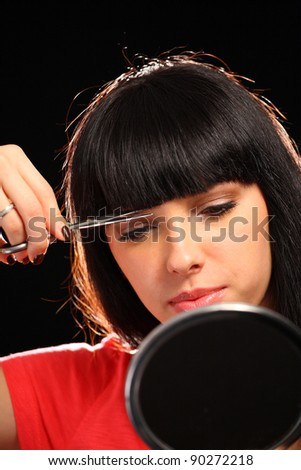 Young woman with scissors cutting her hair - stock photo