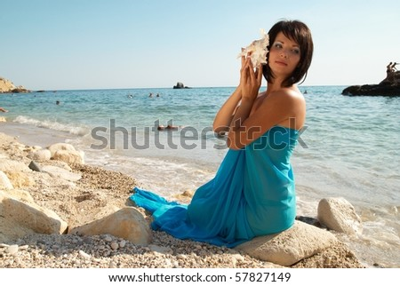 Young woman with seashell on the sunny beach - stock photo